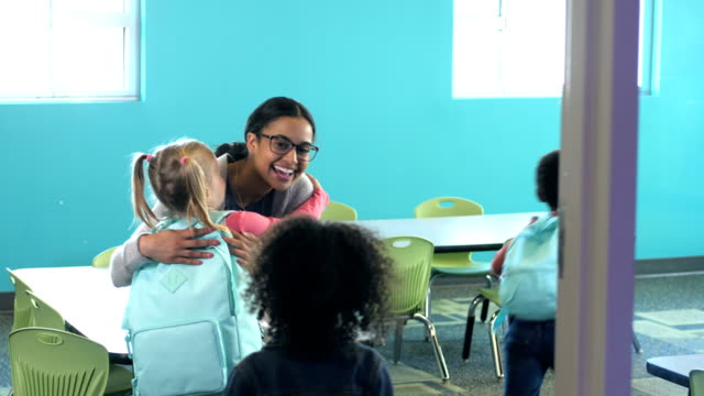 teacher greets preschoolers entering classroom - insegnante video stock e b–roll