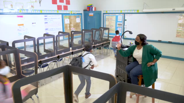 teacher greets students back to school during covid-19 - primary age child stock videos & royalty-free footage