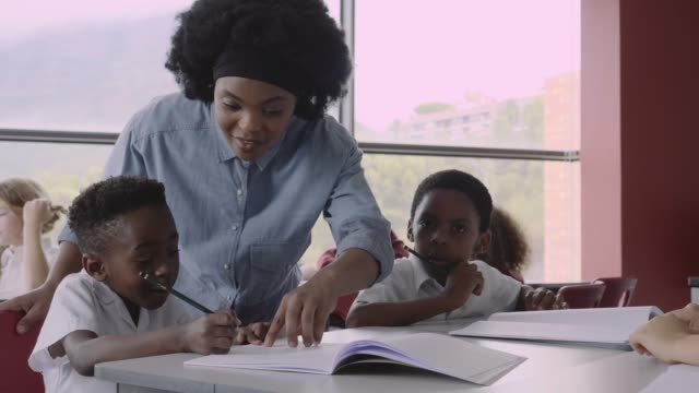 teacher guiding boy writing in book at desk - schoolgirl stock videos & royalty-free footage