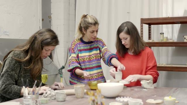 vídeos de stock e filmes b-roll de teacher guiding students in making pottery - professora