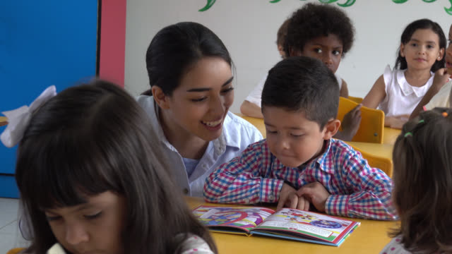 teacher helping a student read a book while laughing - aula video stock e b–roll