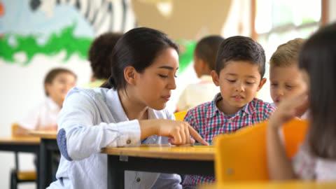 vídeos y material grabado en eventos de stock de ayudar a un estudiante a entender la tarea docente - maestro