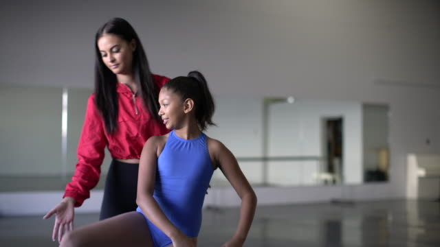 vídeos de stock e filmes b-roll de ms teacher helping a young gymnast with her routine. - professor