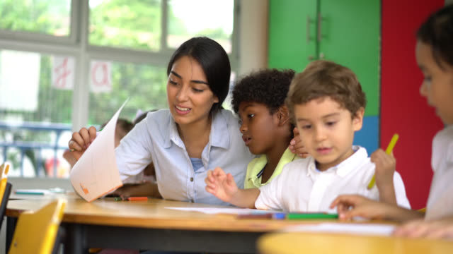 teacher helping an african american boy at class - insegnante video stock e b–roll