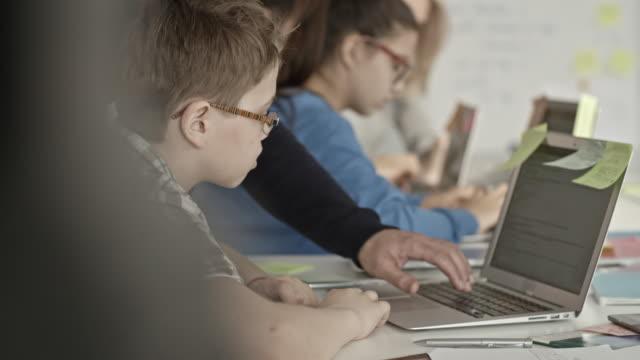 IT teacher helping boy in glasses working on laptop