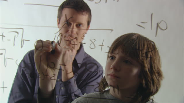 MS Teacher helping boy solve long math problem using marker on glass/ New York City