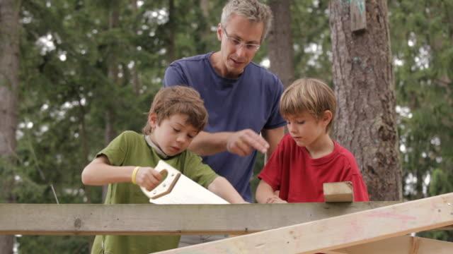 la teacher helping children saw a board / vancouver, british columbia, canada - assistans bildbanksvideor och videomaterial från bakom kulisserna
