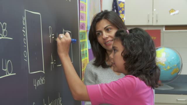 MS, PAN, Teacher helping girl (10-11) solve math equation on blackboard, Richmond, Virginia, USA