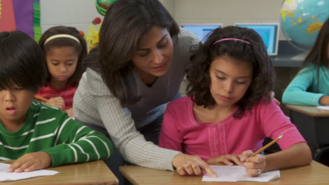 MS, PAN, Teacher helping school pupils (8-11) write test in classroom, Richmond, Virginia, USA