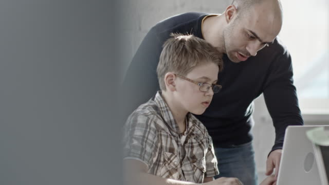 IT teacher helping schoolboy with laptop during lesson