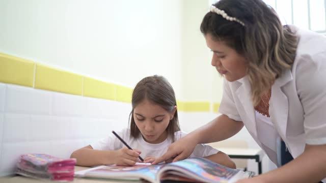 vídeos de stock e filmes b-roll de teacher helping student in the classroom - professora
