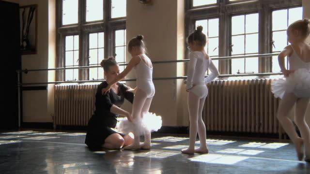 stockvideo's en b-roll-footage met ws slo mo teacher helping students (4-7) get into the their tutus during ballet class / chicago, illinois, usa - gympak