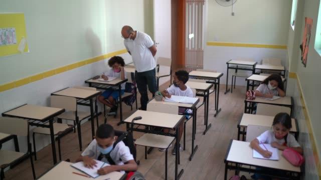vídeos de stock e filmes b-roll de teacher helping students in the classroom - américa latina