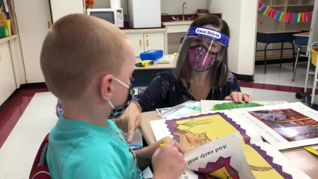 teacher helping students whilst they both wearing protective masks on september 16, 2020. most students there are taking part in a hybrid model,... - teacher stock videos & royalty-free footage