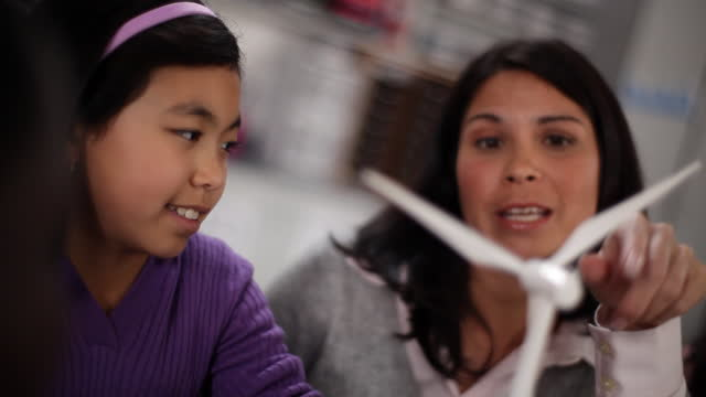 a teacher helps a young student understand a model turbine. - architectural model stock videos and b-roll footage