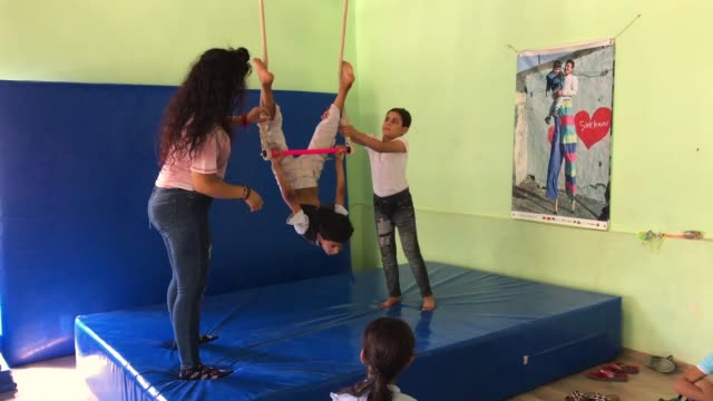 A teacher helps boys learn the trapeze during a workshop at the Mardin Sirkhane Center on July 23 2018 in Mardin Turkey The circus school or Her...