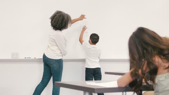 教師は小学生が加算問題を解決するのを助ける - プラス記号点の映像素材/bロール