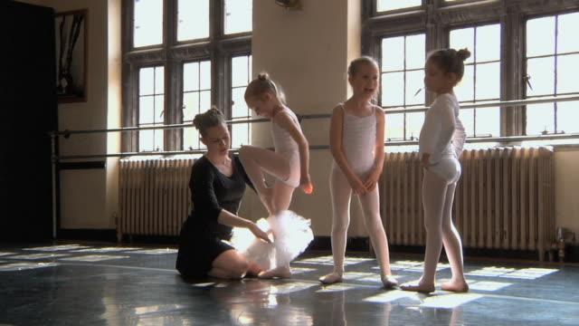 vídeos de stock, filmes e b-roll de ws slo mo teacher helps her students (4-7) get into their tutus in ballet studio / chicago, illinois, usa  - balé