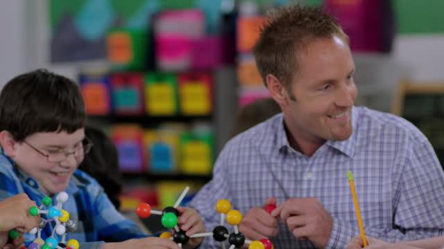 Teacher helps students assemble molecule model