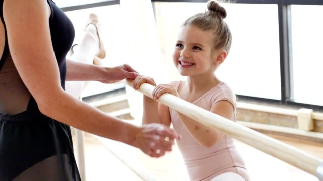 Teacher helps young ballerina while using ballet barre