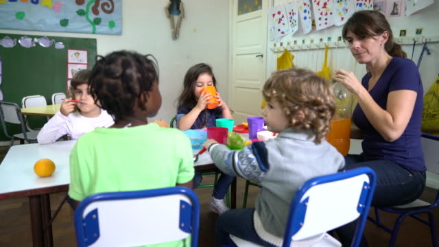 Teacher holding drink sitting with preschool kids