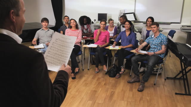 WS Teacher holding sheet of music standing in front of class / London, England