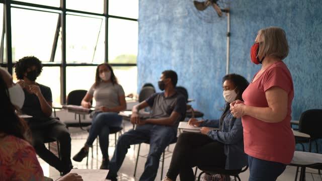 生徒を教えるクラスの前で教師 - フェイスマスクを着用 - support点の映像素材/bロール