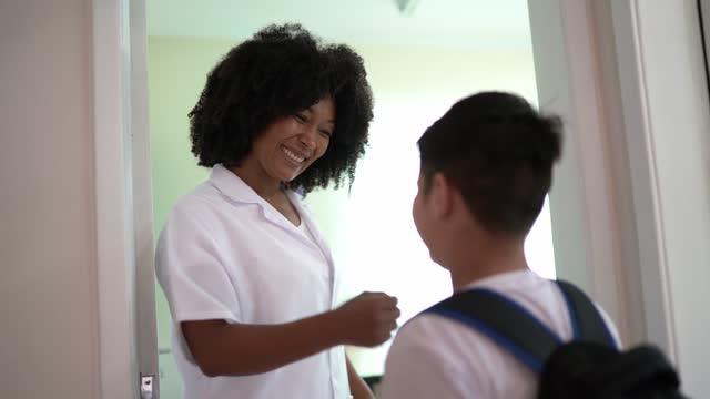 vídeos de stock, filmes e b-roll de professor na porta da sala de aula cumprimentando e abraçando os alunos enquanto eles estão chegando - respect