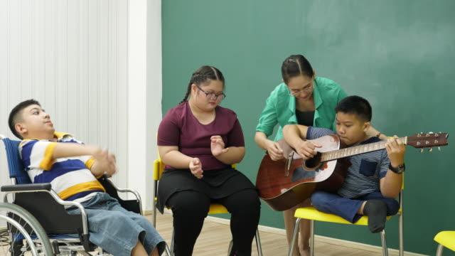 教師は障害のある子供と教室でギターを教えているし、非常に幸せ - 障がい点の映像素材/bロール