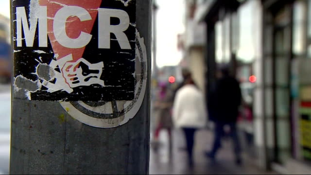 teacher jamshed javeed admits terrorism charges england greater manchester ext close shot of sticker 'mcr' on post as man walks past beside focus... - soft focus stock videos & royalty-free footage