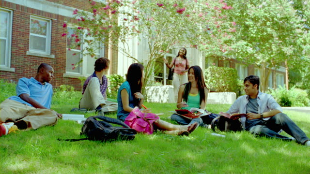 MS, PAN, teacher joining student studding on grass on campus, San Antonio, Texas, USA