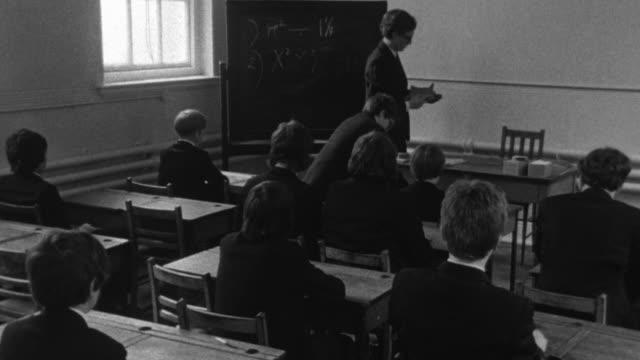 1976 B/W Teacher leads students in prayer in classroom / Liverpool, Merseyside, England