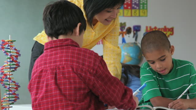 MS PAN Teacher leaning and talking to two boys (6-7) writing in classroom / Jersey City, New Jersey State, USA