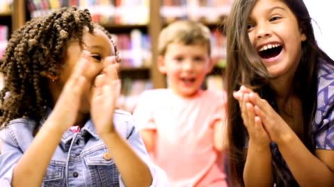 lärare, bibliotekarie läser bok till grundskoleelever i biblioteket eller klassrummet. - grundskola bildbanksvideor och videomaterial från bakom kulisserna