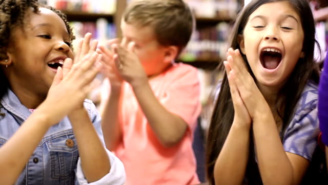 teacher, librarian reads book to elementary students in library or classroom. - elementary age stock videos & royalty-free footage