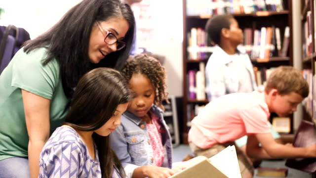teacher, librarian reads book to elementary students in library or classroom. - librarian stock videos & royalty-free footage