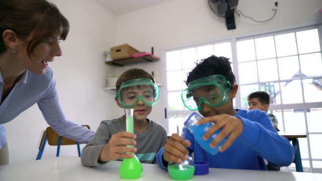 teacher looking at boy pouring chemical by friend - elementary school stock videos & royalty-free footage