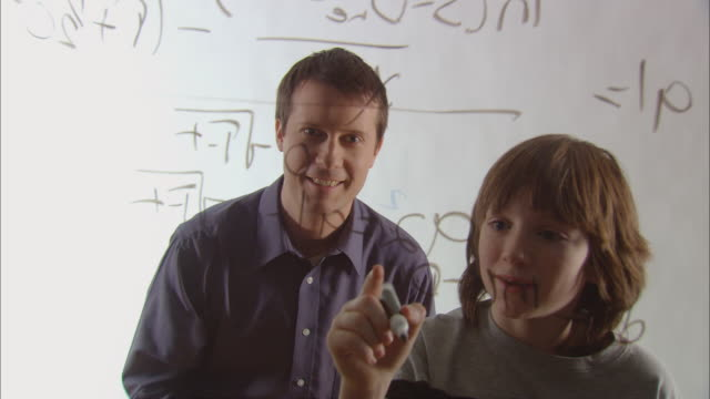 MS Teacher looking over boy's shoulder, helping him solve long math problem using marker on glass/ New York City