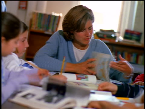 canted teacher looking through books at table with students writing in  classroom - 女性教師点の映像素材/bロール