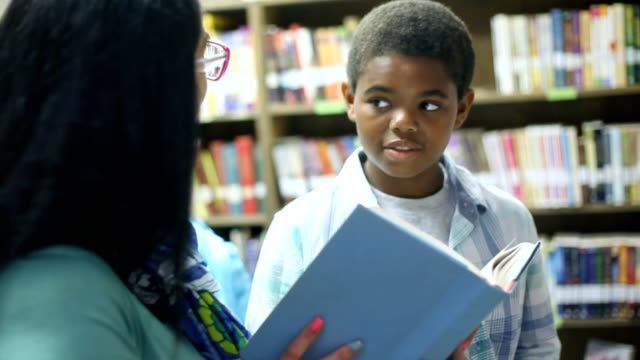 Teacher, mentor helps elementary-age boy select library book