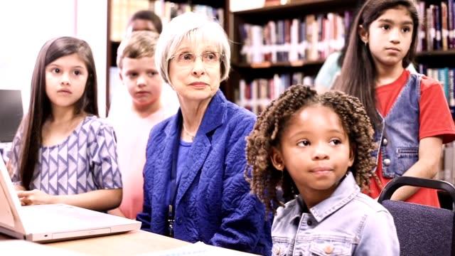 Lehrer, Mentor hilft Grundschulkind Schule Kinder bei den Hausaufgaben.