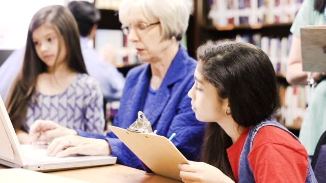 vídeos de stock, filmes e b-roll de professor, mentor ajuda crianças de escola elementar-idade com dever de casa. - criança de escola fundamental