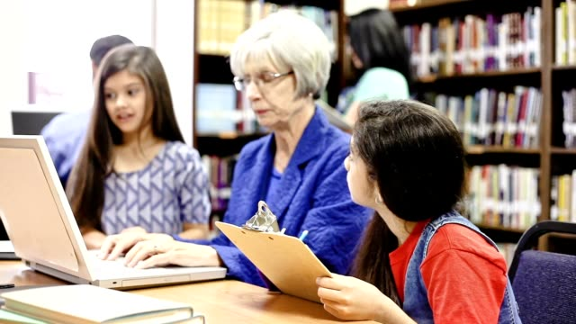 teacher, mentor helps elementary-age school children with homework. - librarian stock videos & royalty-free footage