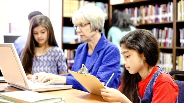Teacher, mentor helps elementary-age school children with homework.