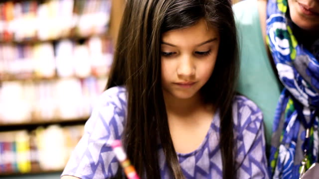 teacher, mentor helps elementary-age schoolgirl with homework. - schoolgirl stock videos & royalty-free footage
