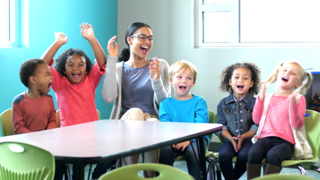 teacher, multi-ethnic group of preschoolers in classroom - in a row stock videos & royalty-free footage