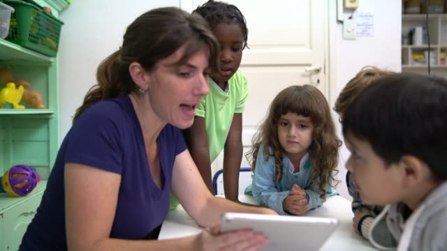 teacher narrating story with digital tablet - narrating stock videos & royalty-free footage