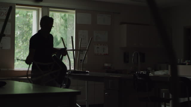 vídeos de stock e filmes b-roll de teacher opening up empty classroom and putting down chairs - cadeira