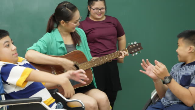 teacher playing guitar in classroom with disabled child and very happy - music therapy stock videos & royalty-free footage