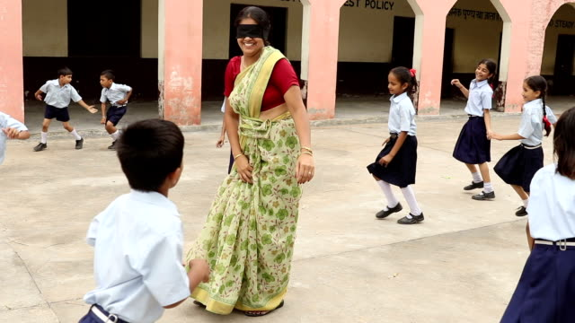 Teacher playing with school students at school campus, Haryana, India